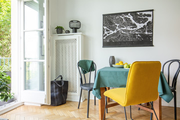 Map poster hanging on white wall in real photo of dining room interior with balcony, herringbone parquet, table with fruits and tablecloth with black and yellow chairs