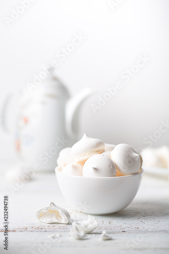 Poster Meringues sweet dessert and teapot on white wooden table