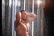 Adult sexual caucasian gay, bodybuilder, with brown wet hair, taking a shower with water drops on his oiled muscular body against black tile wall with running water background