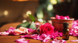 Clay bowl and aroma oil dark glass bottle among roses petals on the wooden table, natural raw material, selected focus - 232500515