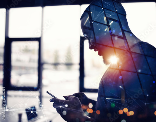 Foto Murales Businessman works with his smartphone in office. double exposure