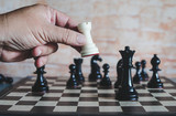 hand of businessman moving chess figure to win competition play. ,business strategy success concept.