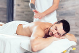 masseur preparing his hands for massage while his clent li lying with closed eyes. close up side view photo - 232520344