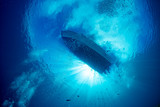 boat ship from underwater blue ocean with sun rays - 232520924