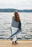 Redhead woman wrapped in plaid standing on the pier of the lake in autumn and looking faraway. - 232527185