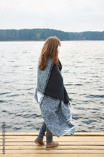 Foto Murales Redhead woman wrapped in plaid standing on the pier of the lake in autumn and looking faraway. Autumn cloudy nasty weather.