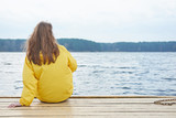 Redhead woman in yellow raincoat sitting on the pier of the lake and looking faraway. - 232527380