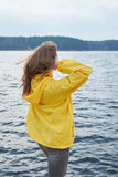 Redhead woman in yellow raincoat stranding near the lake and looking faraway. Cloudy nasty autumn weather. - 232527506