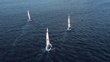 left to right swing of three two-manned sailboats - 232529595