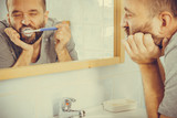 Bored guy brushing his teeth in bathroom - 232532937