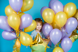 Happy little girl with balloons on a blue background - 232533978