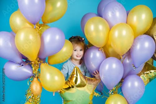 Happy little girl with balloons on a blue background