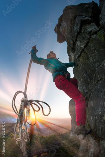 Leinwandbild Motiv Climber at the top of the mountain at night.