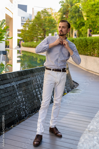 Portrait of young bearded fashionable man outdoors
