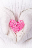 Hands in white knitted mittens holding pink wicker heart. - 232553989