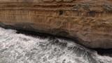 Ocean waves crashing against rock face. Aerial views. - 232562319