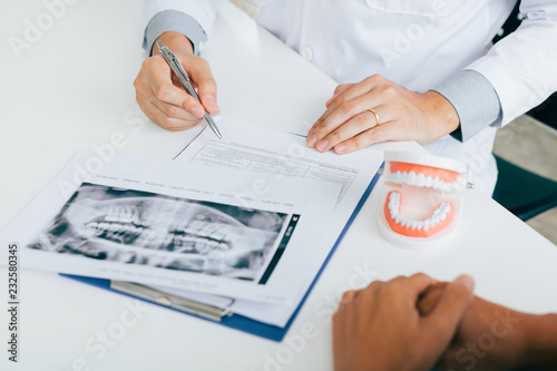 Dentist hand holding pen pointing x-ray picture and talking to the patient about medication and surgery treatment. - 232580345