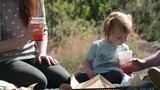 Woman drinking from straw as daughter blows into straw creating bubbles in her aunts drink. - 232588718