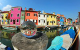 houses on the island of Burano near Venice in Italy and a glass sphere with the reflection of the village - 232597550