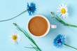 Leinwanddruck Bild - Spring background. Cornflowers, chamomile and a cup of hot coffee on a blue background. Top view