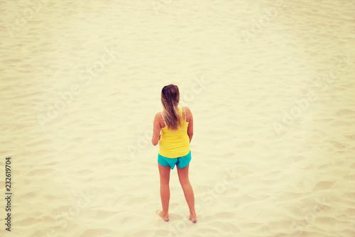 Leinwanddruck Bild Tired woman standing on the beach
