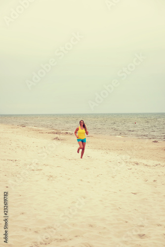 Leinwanddruck Bild Young woman running on the beach