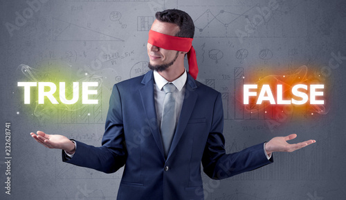 Leinwandbild Motiv Businessman with red ribbon on his eye deciding true or false