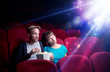 Leinwandbild Motiv Romantic couple cuddling and watching the miraculous part of the film