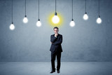 Handsome businessman in an empty space with bulbs above and uninspired face  - 232630198