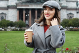Smiling stylish young woman drinking coffee while walking on a city street - 232633522