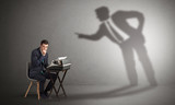 Little man working and a big shadow arguing with him  - 232637306