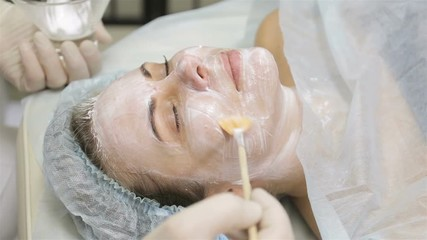 Woman getting face peeling mask in spa beauty salon by beautician © hdesert