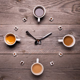 Coffee cups and sugar cubes form a clock on the rustic wooden table