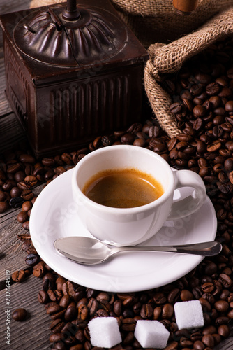 on the rustic wooden table, in the foreground, a small cup of creamy espresso. In the background an old grinder with roasted coffee beans. Vertical composition © luigi giordano