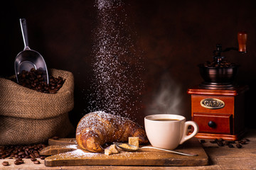 Cup of hot coffee, croassant dusted with veiled sugar, wooden grinder, and jute bag with roasted coffee beans