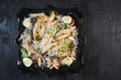 Delicious fresh caesar salad with chicken and eggs in a black plate on a black stone table background - 232672700