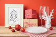 Christmas dinner table setting with empty plate and decorations