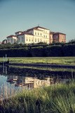 Palace and gardens of Reggia di Venaria near Turin, Italy, reflecting in water pond in a sunny summer day