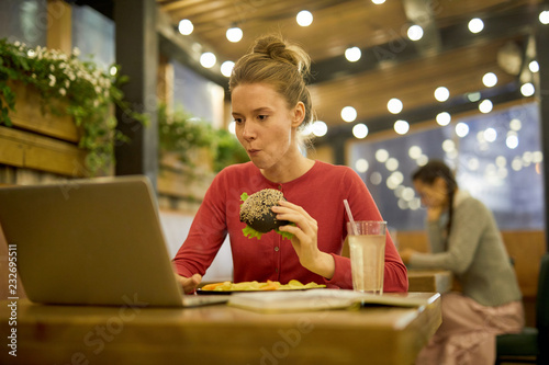 Poster Hungry girl eating cheeseburger and french fries in college cafe while searching for information in the net