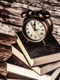 Alarm clock and books on wooden table and background - 232695785