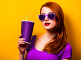 Style redhead girl in purple dress and sunglasses with drink on yellow background. - 232696179