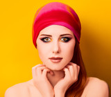Portrait of a young woman with makeup in pink head scarf on yellow background. - 232696194