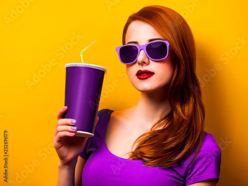 Stylowa rudzielec dziewczyna w purpurach ubiera i okulary przeciwsłoneczni z napojem na żółtym tle.