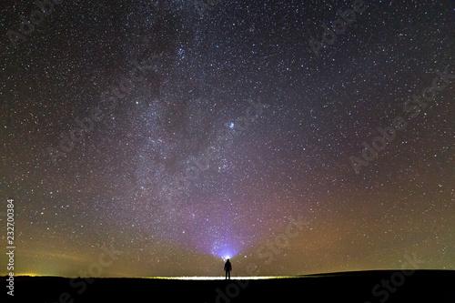Black silhouette of man with head flashlight on grassy field under beautiful dark summer starry sky.