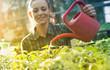Leinwanddruck Bild - Woman watering seedlings in greenhouse