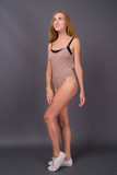 Young beautiful woman with blond hair wearing leotard against gr - 232704181