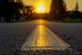 Close-up of a road, sun setting on the horizon - 232714532