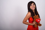 Studio shot of young happy Persian woman smiling while thinking  - 232716158