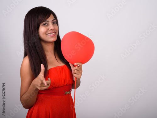 Studio shot of young happy Persian woman smiling while pointing