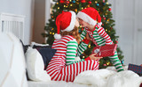 py family mother hug her baby son  in pajamas opening gifts on christmas morning near   tree - 232719307